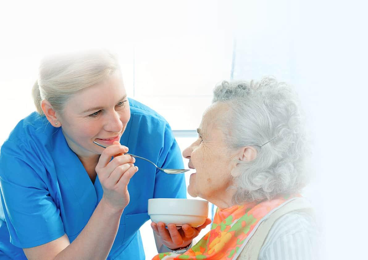 caregiver feeding a senior woman