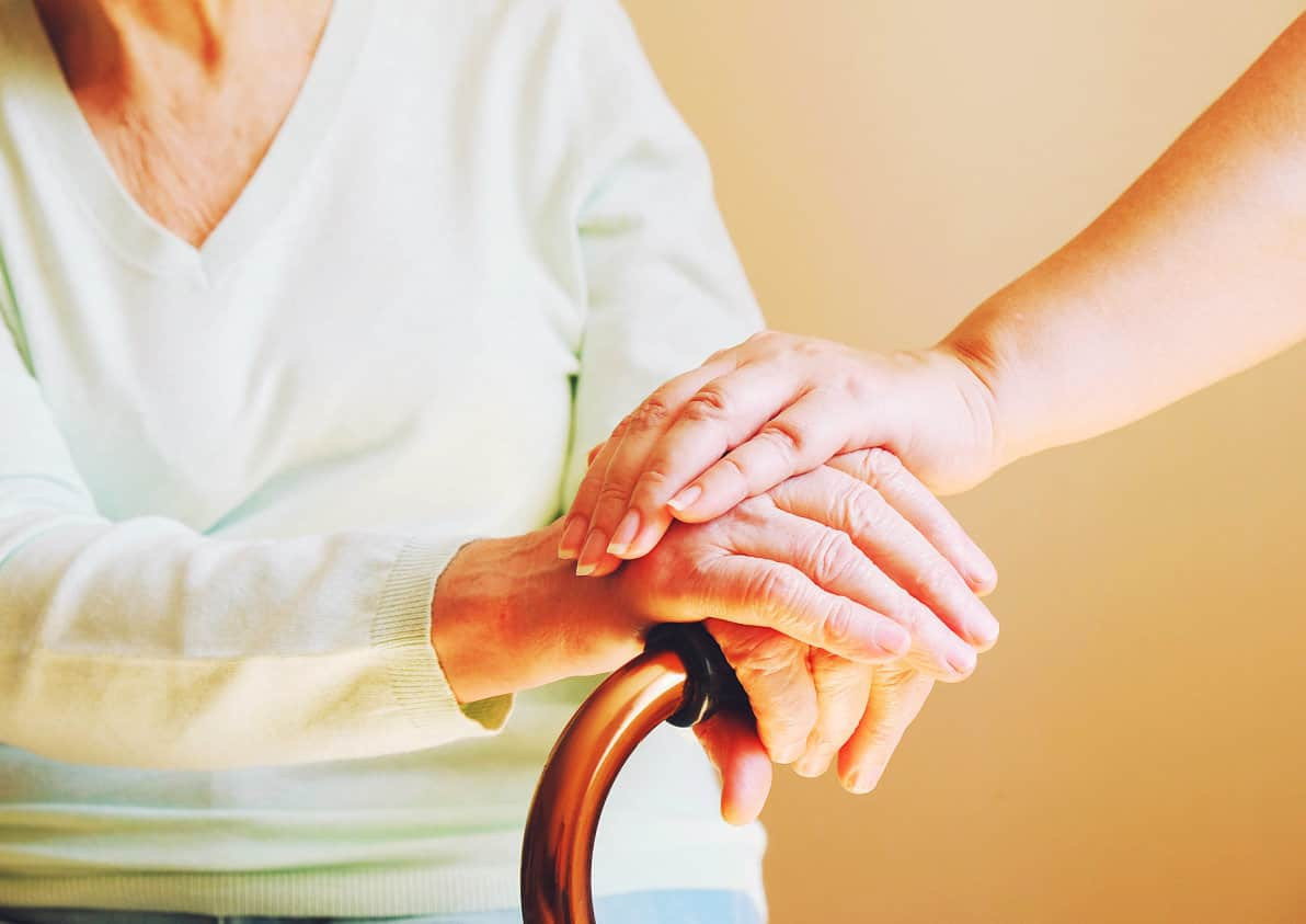 crop image of a woman holding a hand of a senior woman
