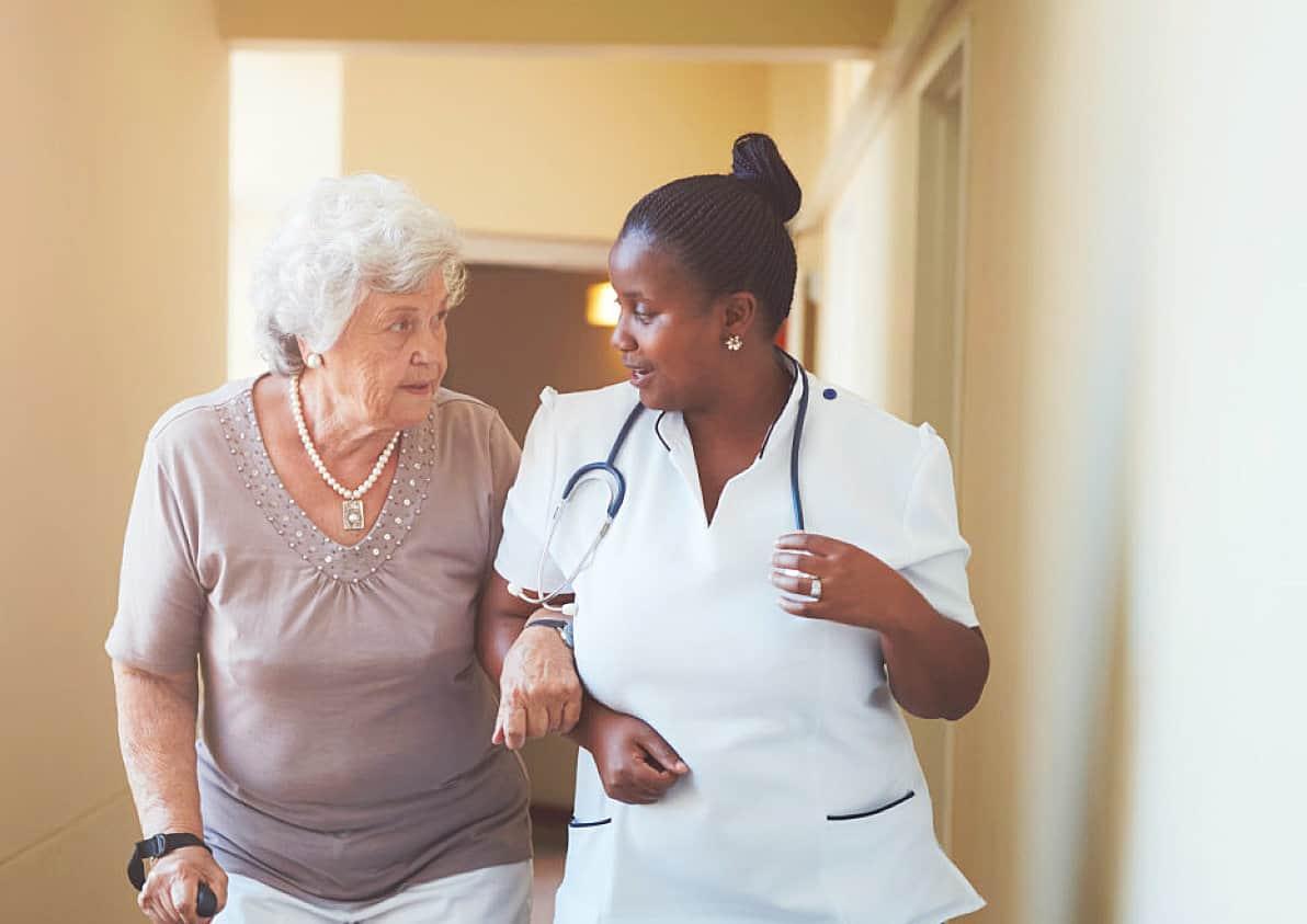 nurse and senior woman talking on the hallway