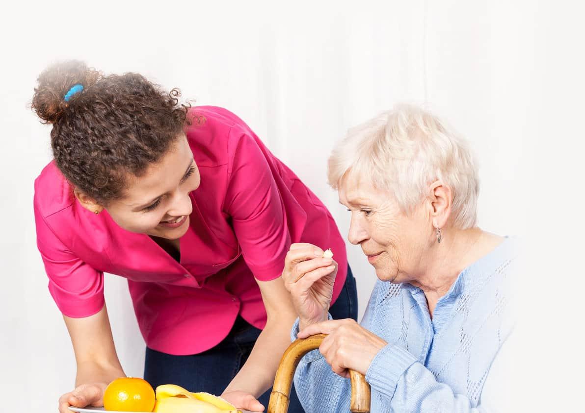 caregiver serving food to her patient