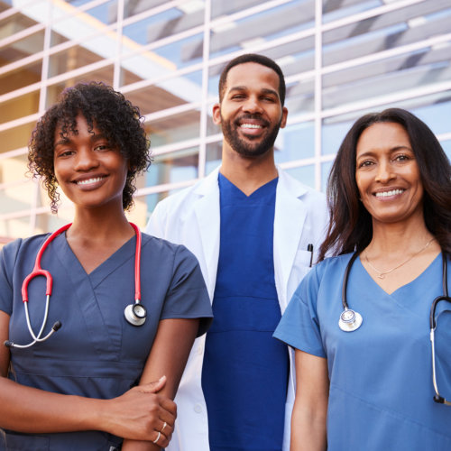 Three healthcare colleagues standing outside modern hospita