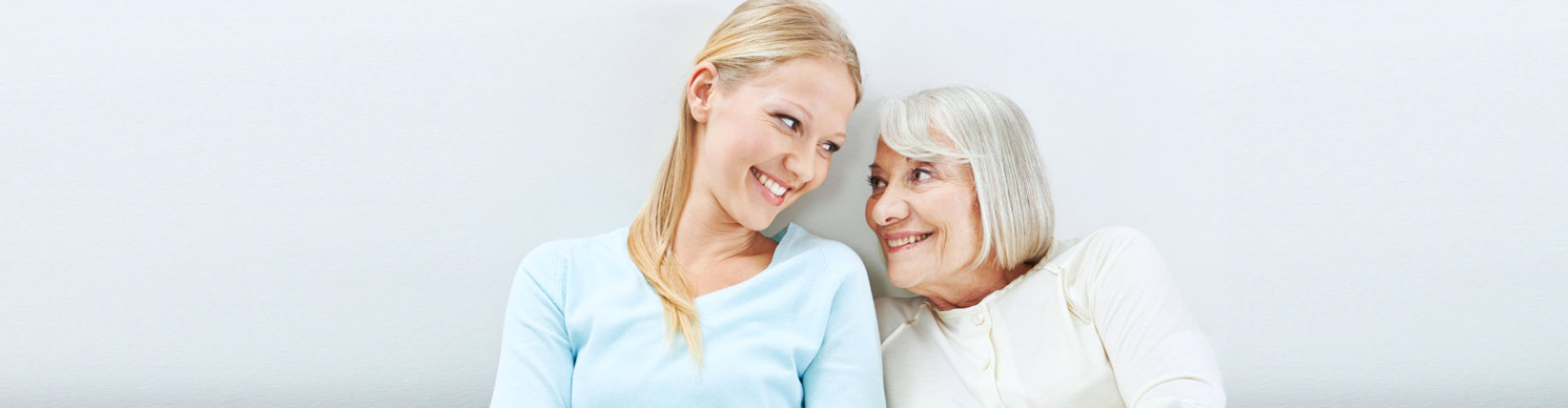 caregiver and a senior woman smiling to each other