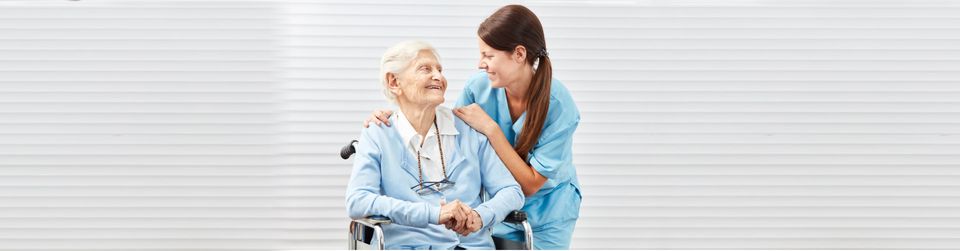 caregiver with an senior woman in wheelchair